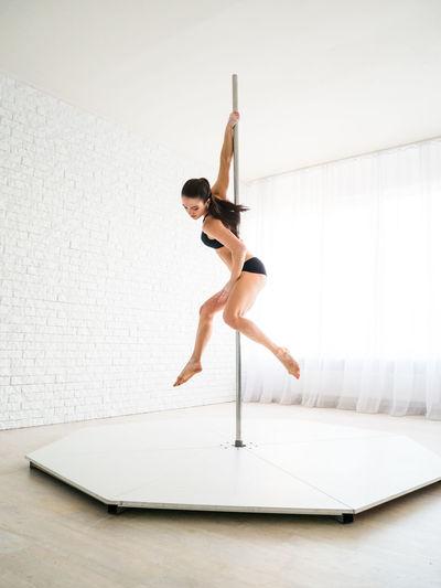 Woman doing pole dance against brick wall