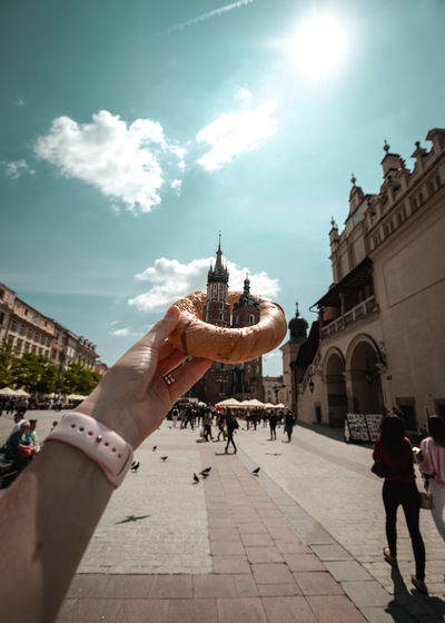 Cropped hand of woman holding donut against building against sky