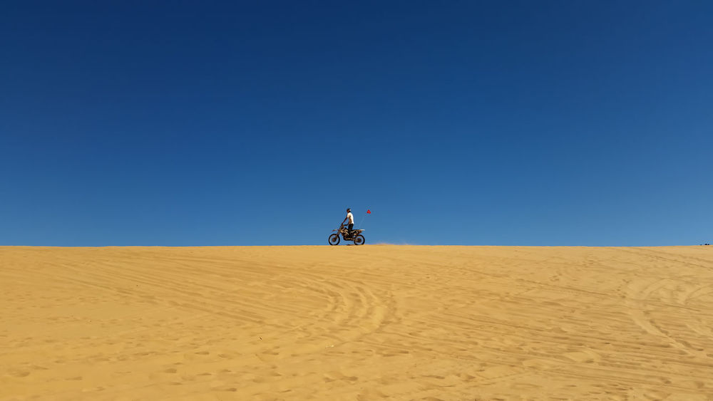 Dirt bike rider at the top of a sand dune Coral Pink Sand Dunes State Park Motorbike Rider Motorcycle Navajo Sandstone Utah Adventure Arid Climate Clear Sky Desert Desert Beauty Dirt Bike Rider Extreme Sports Horizon Over Land Landscape Motorsports negative space One Person Outdoors Remote Sand Sand Dune Sand Dunes Scenics Solitude Travel Destinations An Eye For Travel Summer Exploratorium