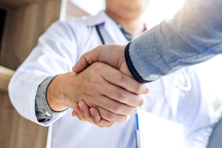 Midsection Of Doctor And Patient Shaking Hands