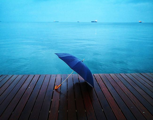 Umbrella at the seaside EyeEmNewHere Blue Water Sea Sky Umbrella Seaside Lonely Blue Rain Rainy Day Water Sea Blue Horizon Over Water