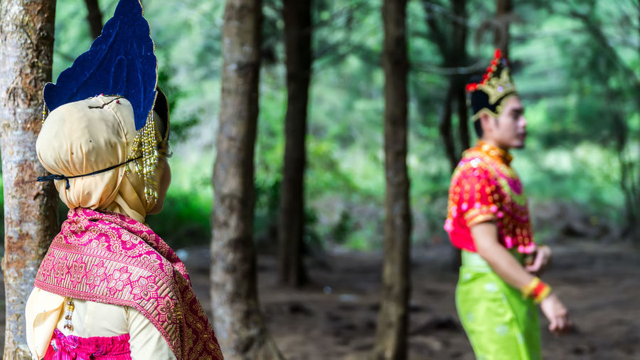 Man and woman in traditional clothing at forest
