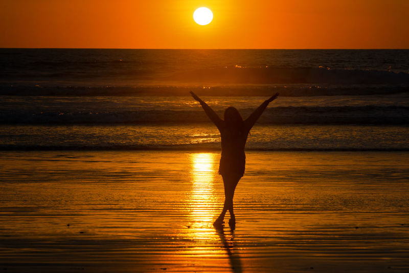 Silhouette of a beautiful young woman on a beach in Montanita, Ecuador at sunset Beach Busy Carnival Coast Crowd Crowded Destination Ecuador Montañita Montañita,Ecuador Ocean People Quito Scene Sea Summer Sun Sunbathing Sunny Sunset Tourism Tourist Travel Vacation Water