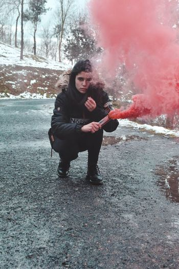 Full Length Portrait Of Woman Holding Distress Flare On Road