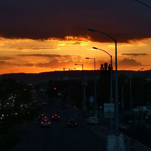 Cars on street against dramatic sky during sunset