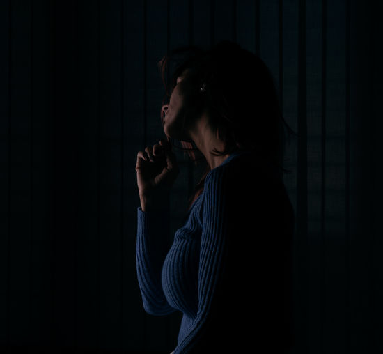 Portrait of a beautiful young woman standing against black background