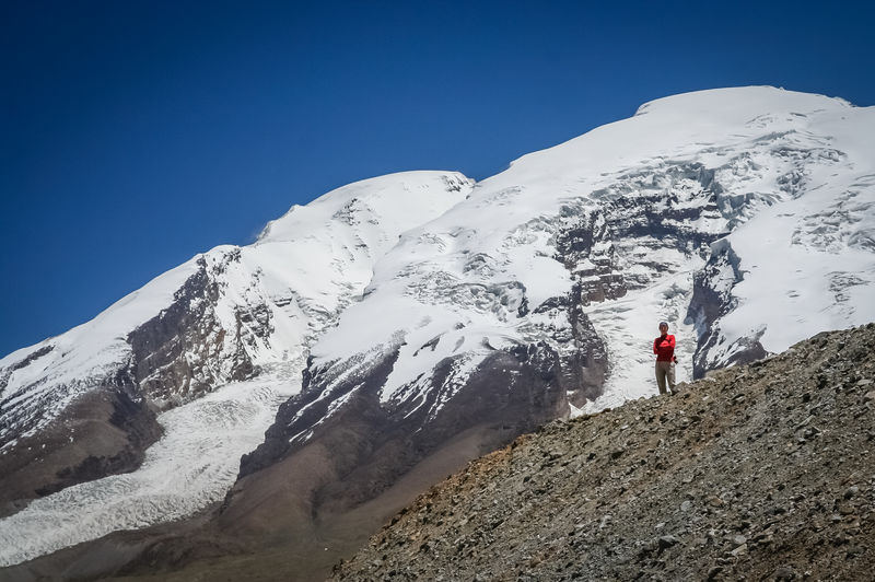 Low angle view of woman standing on rock against snowcapped mountain