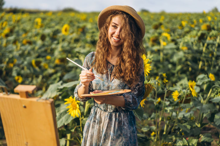 Young woman holding sunflower while standing against yellow flowers