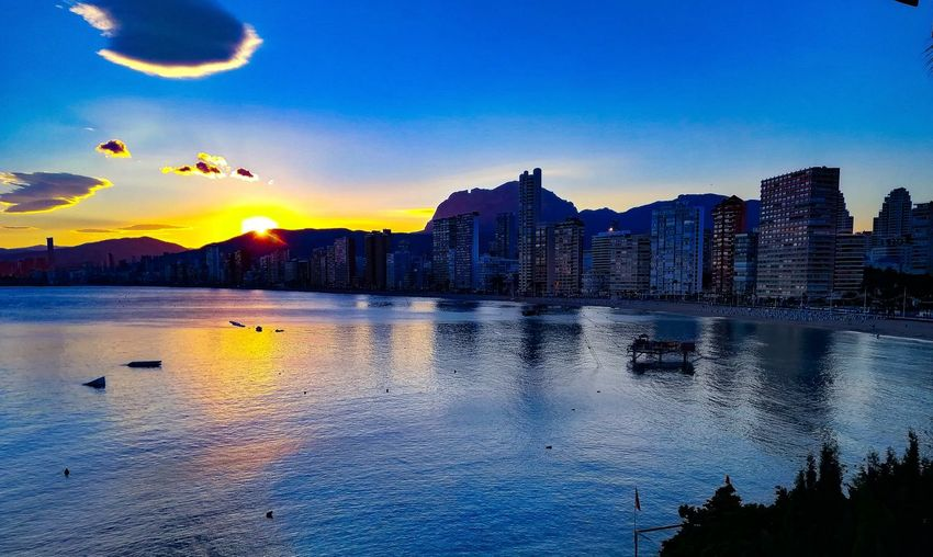 Scenic view of sea and buildings against sky at sunset