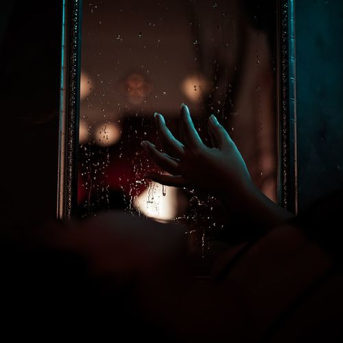 Person seen through wet glass window