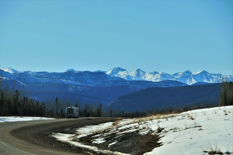 RV traveling down winding road in Canada Sky Scenics - Nature Beauty In Nature No People Tranquil Scene Tranquility Nature Mountain Mountain Range Cold Temperature Winter Clear Sky Snow Copy Space Day Snowcapped Mountain Outdoors Travel Camper Recreational_vehicle Rv Road Road Trip
