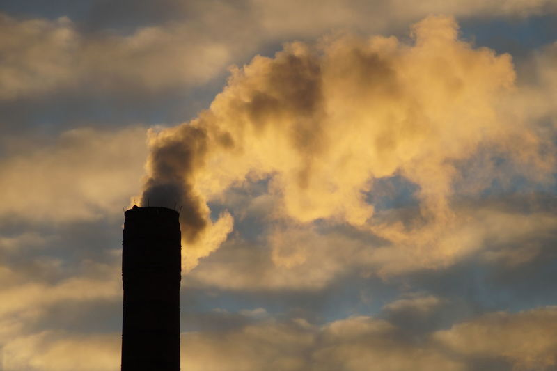 Low Angle View Of Smoke Stack Against Sky During Sunset