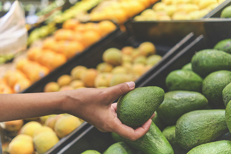 Cropped image of hand holding fruits at market stall
