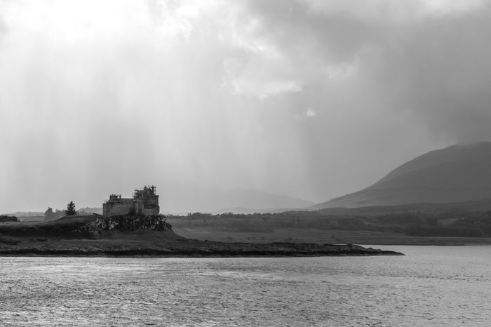 Isle of Mull, Scotland - a dramatic sky over a castle on an island viewed from the water, black and white Black & White Blackandwhite Blackandwhite Photography Castle Cloud - Sky Clouds And Sky Dramatic Sky Monochrome Outdoor Photography Outdoors Scenics Scotland Sea Sky Tranquility Waterfront