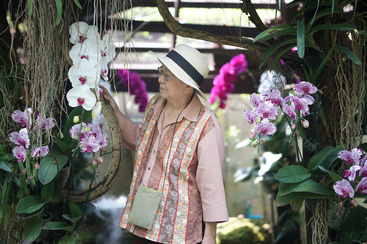 Woman standing by pink flowering plants