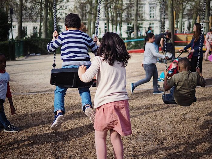 Rear view of children playing at park
