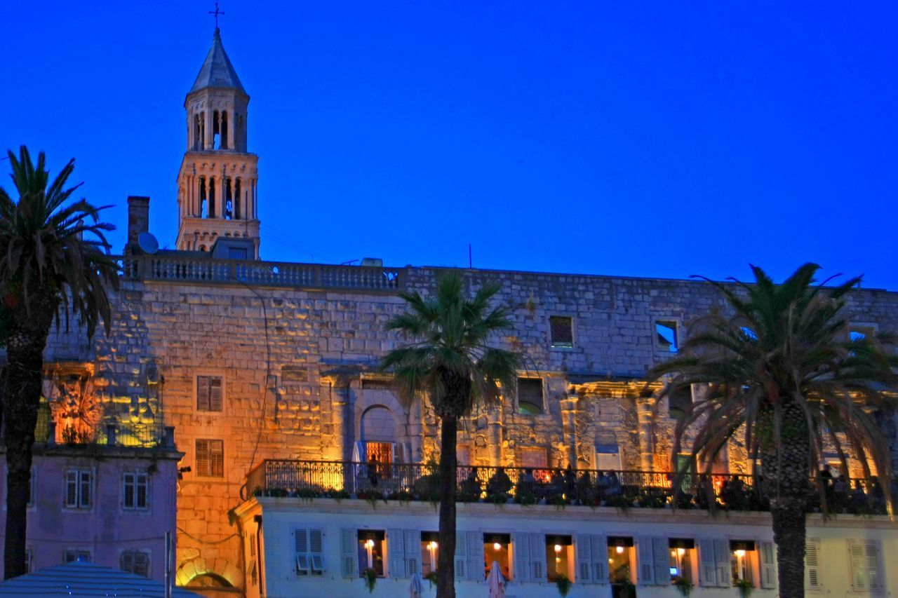 architecture, building exterior, built structure, blue, illuminated, tree, place of worship, religion, night, no people, outdoors, palm tree, low angle view, clear sky, clock tower, spirituality, travel destinations, sky, city, clock