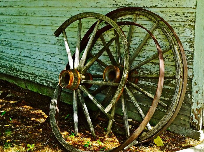 Abandoned wheels by wooden wall