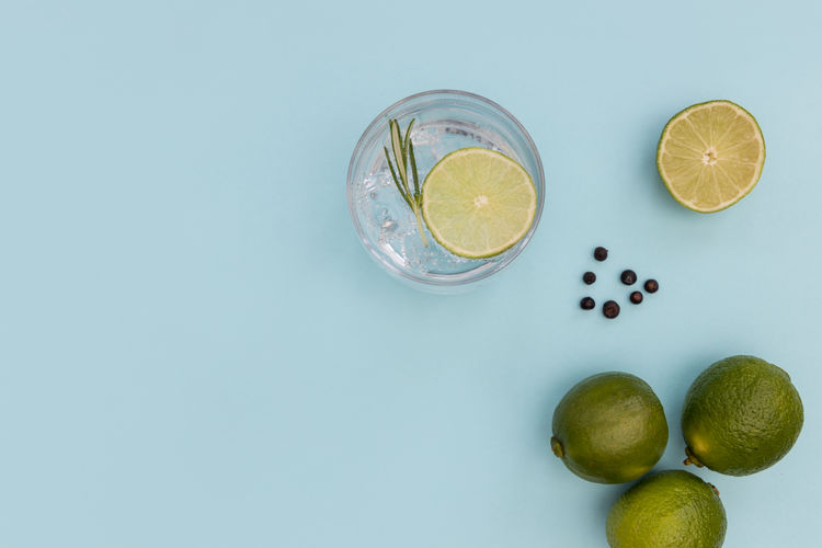 Gin tonic cocktail drink in glass on summer blue background GIN Tonic Cocktail Drink Glass Ice Cold Blue Background Minimal Summer Top View Overhead Above Flat Lay Lime Green Lemon Cucumber Juniper Berries Alcohol SLICE Fruit Botanical Beverage Leaf Color Refreshment Mint Rhubarb Bubbles Sparkling
