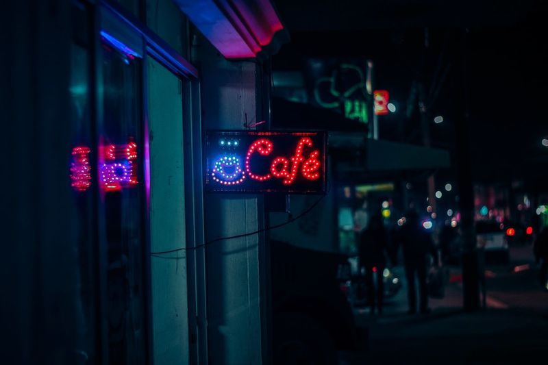 Illuminated sign with cafe text in city at night