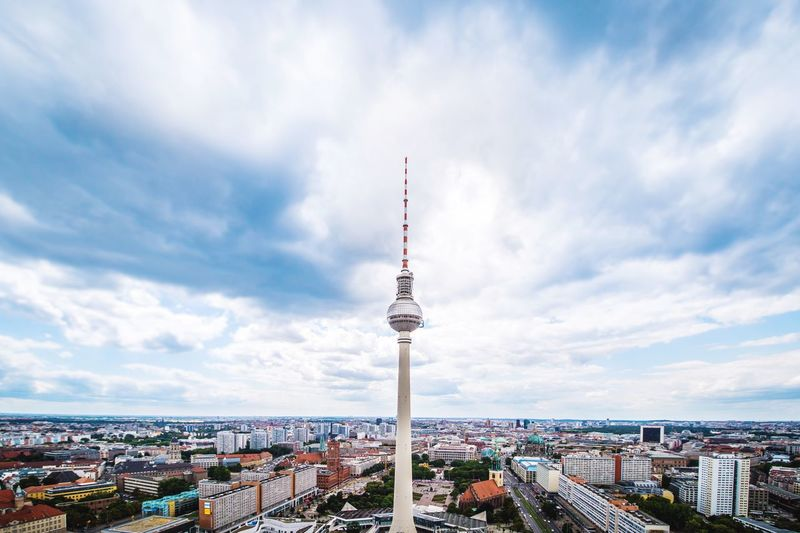 High section of fernsehturm amidst town against cloudy sky