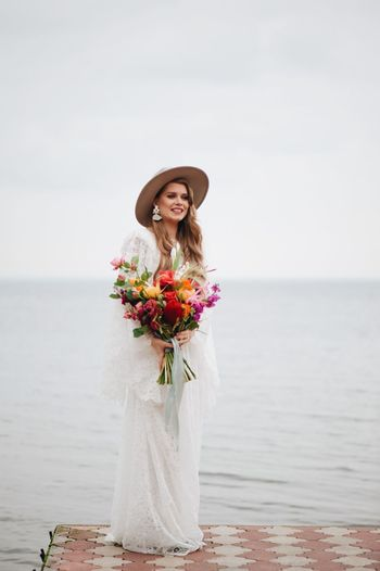 Bride standing on pier in sea during wedding ceremony