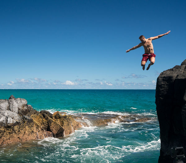 Young man jumping in sea from rock against sky