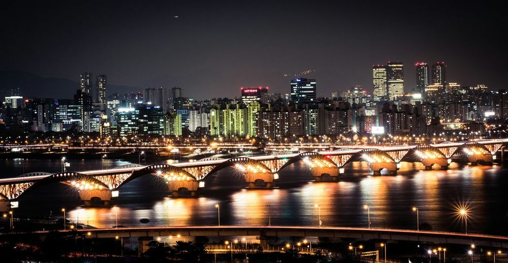 Bridge across river illuminated at night