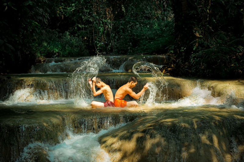 Side view of shirtless male friends splashing water in river