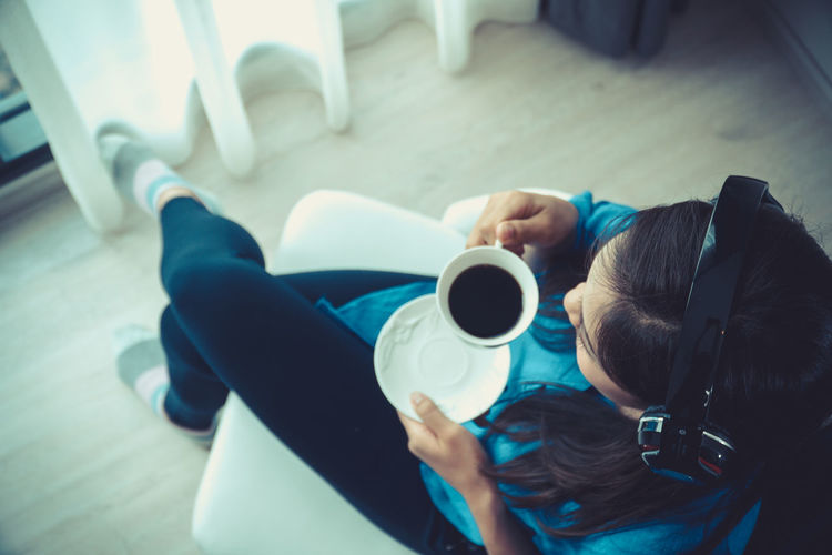 High angle view of woman holding coffee cup while sitting on chair
