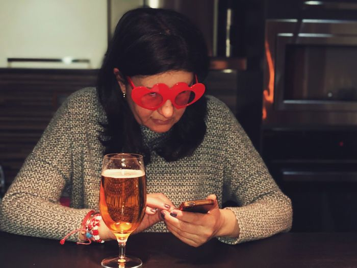 Close-Up Of Woman Using Phone While Having Beer At Table