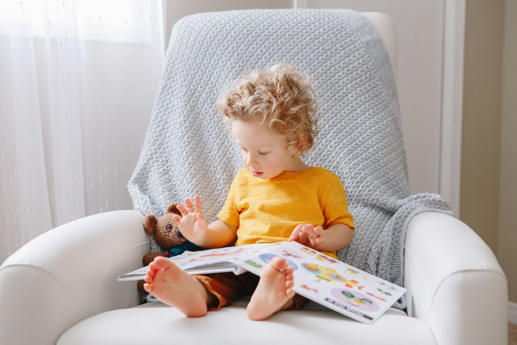Baby boy toddler 2 years old reading book. early age kid child development education