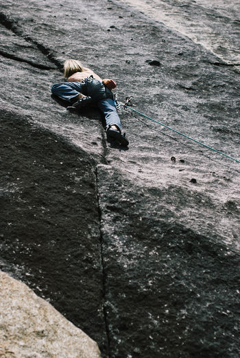 Low Angle View Of Man Rock Climbing On Sunny Day