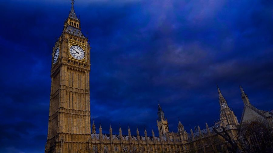 Low angle view of big ben against blue cloudy sky