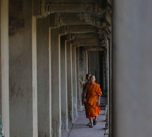 Monks Walking In Corridor Of Temple