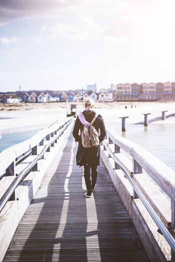 Rear view of mid adult woman with backpack walking on footbridge over sea against sky