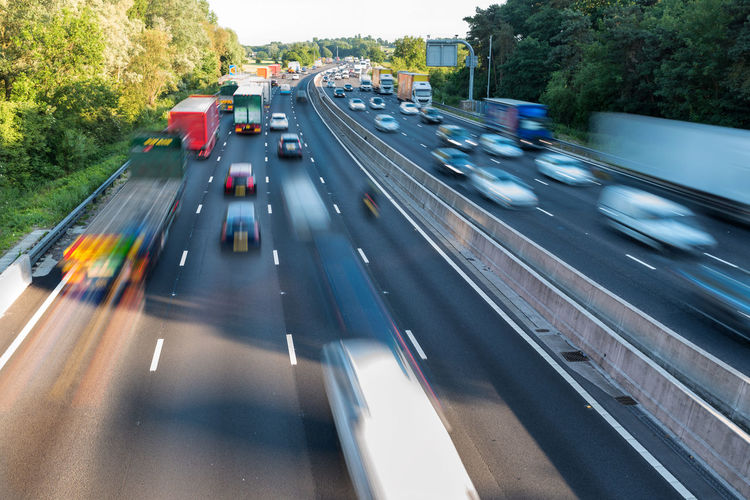 Sunset view heavy traffic moving at speed on UK motorway in England Blurred Motion Car City Day High Angle View Highway Land Vehicle Mode Of Transportation Motion Motor Vehicle Multiple Lane Highway No People on the move Outdoors Road Sign Speed Street Symbol Traffic Transportation Tree