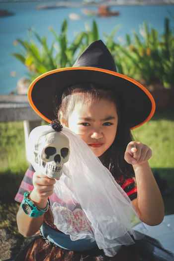 My little witch, Halloween day.. Cosplay Halloween Sunlight Asian Girl Black Hair Boys Child Childhood Clothing Day Females Focus On Foreground Front View Girl Hat Holding Innocence Kid Leisure Activity Lifestyles Little Girl Looking At Camera Magic Males  Men One Person Outdoors Playful Portrait Pre-adolescent Child Real People Skull Smilling Witch Wonder Young Adult