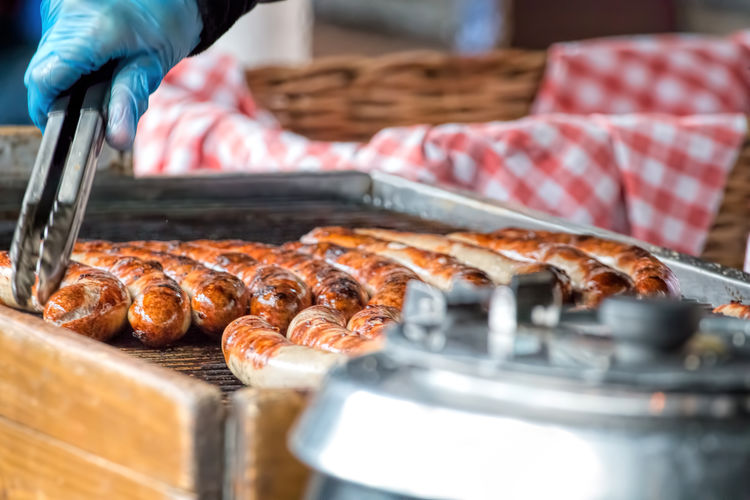 Cropped Image Of Person Roasting Sausage On Barbecue At Market Stall