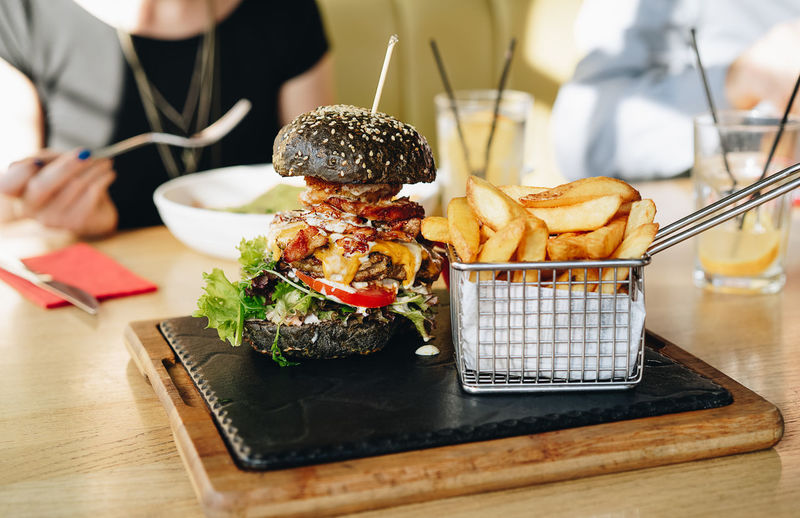 Close-Up Of Burger With French Fries Served On Table In Restaurant