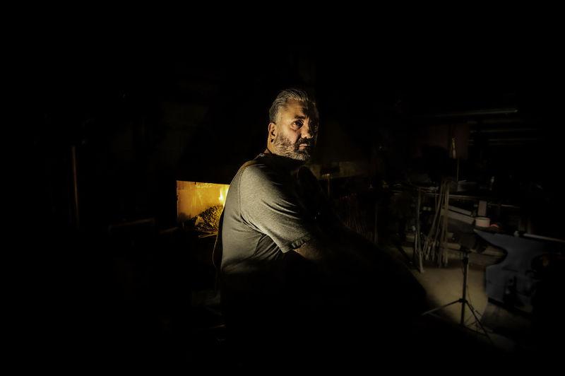 Portrait of man sitting in the dark