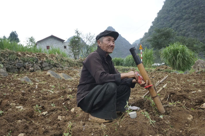 Traditional farming in Dong Van, Vietnam. Farm Farming Vietnamese Dong Van Vietnam One Person Real People Holding Men Nature Day Adult Plant Tree Land Mountain Leisure Activity Lifestyles Full Length Clothing Outdoors Mid Adult Males  Sky