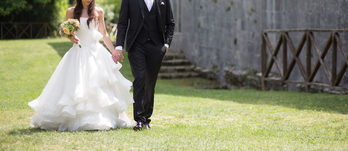 Low Section Of Newlywed Couple Holding Hands And Walking On Grassy Field