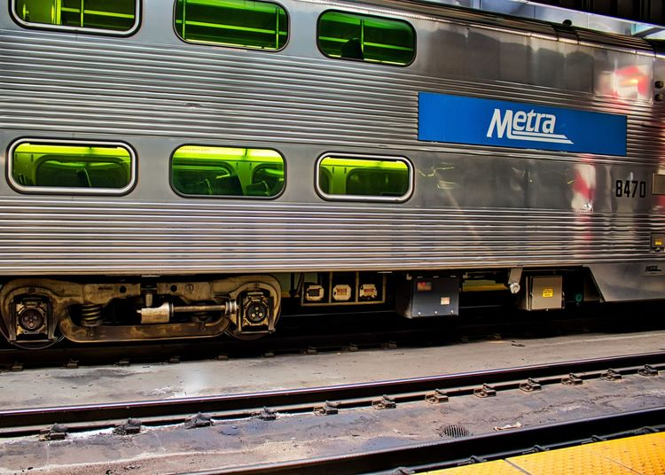 Metra train sitting on tracks at Ogilvie Transportation Center as another engine pulls in and is reflected on train car exterior. Chicago Chicago Loop Communication Land Vehicle Metal Metra Train Mode Of Transportation Number Ogilvie Transportation Center Outdoors Passenger Train Public Transportation Rail Transportation Railroad Car Railroad Station Railroad Station Platform Railroad Track Shunting Yard Station Text Track Train Train - Vehicle Transportation Travel