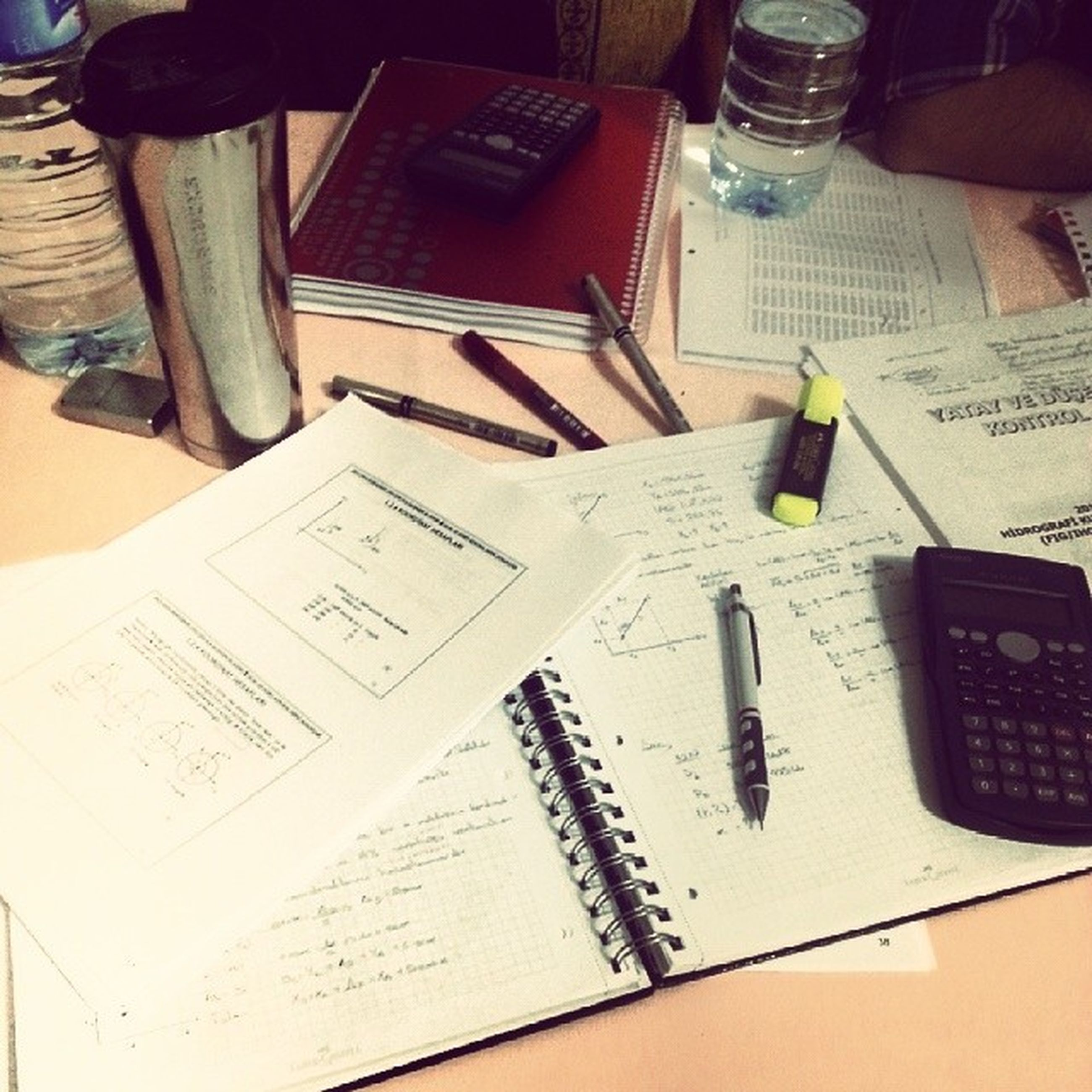 indoors, book, education, communication, paper, text, table, high angle view, document, western script, pen, close-up, learning, desk, still life, laptop, page, writing, technology, wireless technology