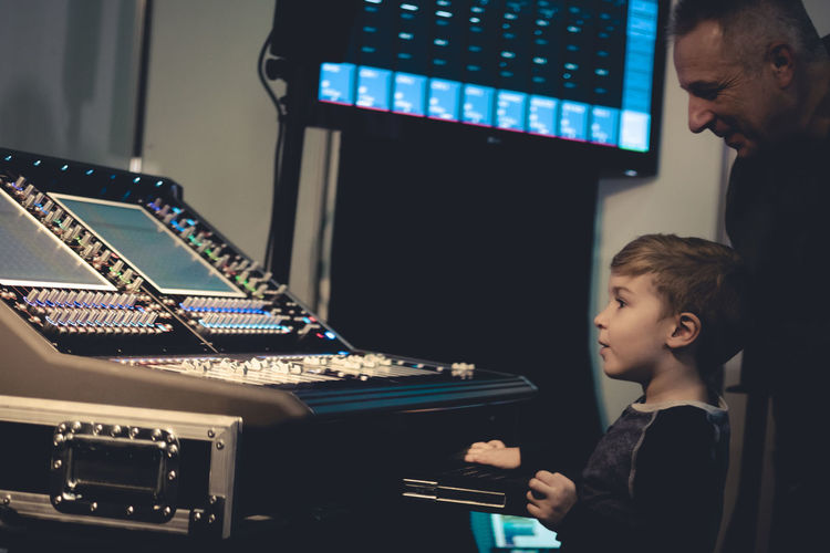 Music teacher and boy standing by sound mixer at recording studio