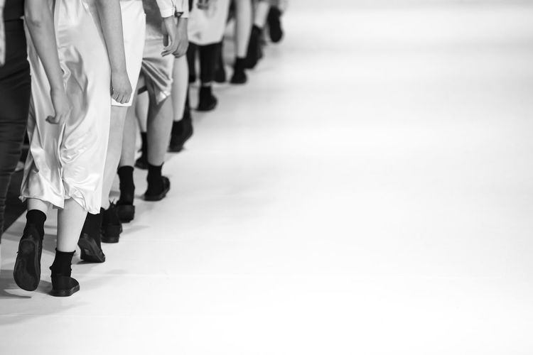 Low section of fashion models walking on runway