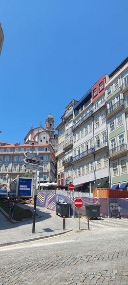 Buildings by street against clear blue sky