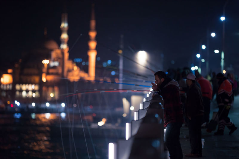 People fishing on illuminated galata bridge at night