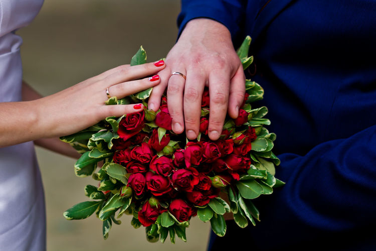 Close-Up Mid Section Of Newly Wed With Bouquet